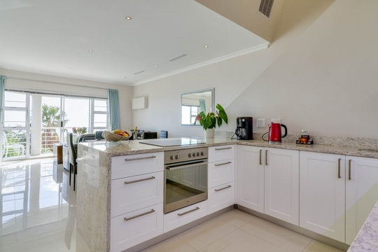 Self catering kitchen leads onto the open plan living area and balcony.